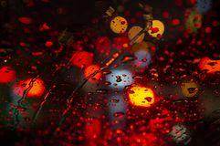 Raindrops on windshield and bokeh lights out of focus. Close up of raindrops on windshield at night in the city royalty free stock image