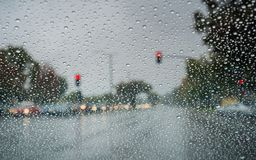 Raindrops on the windshield while driving on a rainy day during fall season, California Stock Photo