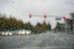 Raindrops on the windshield on a rainy day while stopped at a traffic light; San Francisco bay area; California stock photo
