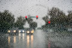 Raindrops on the windshield on a rainy day while stopped at a traffic light; San Francisco bay area; California stock images