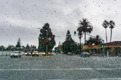 Raindrops on the windshield on a rainy day, traffic light background royalty free stock photo