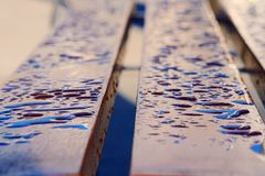 The raindrops on the wooden bench stock photos