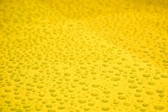 Raindrops on yellow background Royalty Free Stock Images