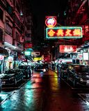 Neon lights in rainy hongkong streets at night stock images
