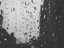 Rainfall on glass. Picture shows how we enjoy rain today by juat watching not feeling it Stock Image