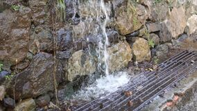 Rainfall wada falls in a stream on a sewer grate near a wall of raw stone