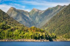 Rainforest and mountain range at Doubtful Sound. On a adventure cruise, a location so remote that can only be reached by water across Lake Manapouri in Royalty Free Stock Image