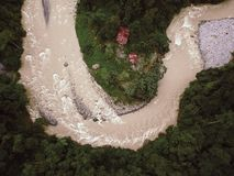Rainforest River in Indonesia threatening to flood Huts. Drone Shot stock photo