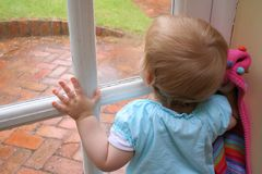 Raining!. Child looking out of a window at the rain, waiting to play outside royalty free stock photos