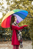 Is it raining. Beautiful young redhead with a rainbow color umbrella  checking with her hand if is it still raining outside Stock Photo
