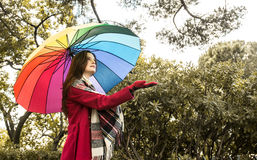 Is it raining. Beautiful young redhead with a rainbow color umbrella  checking with her hand if is it still raining outside Royalty Free Stock Photo