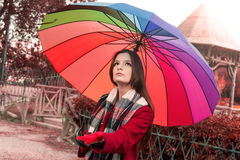 Is it raining. Beautiful young redhead with a rainbow color umbrella  checking with her hand if is it still raining outside Royalty Free Stock Photography