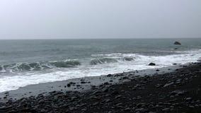 Raining at the black beach. Black sand and beach stones on  overcast day stock video
