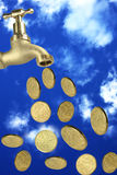 Raining coins. Tap with money falling and blue sky Royalty Free Stock Photography