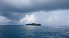 Raining coming middle of the sea and Small island royalty free stock images