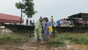 Raining, ferry, mekong, cambodia. Southeast asia,  Cambodia, mekong,  october 2013. Under rain people get off ferry boat at Koh pene island stock video