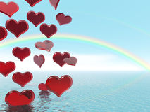 Raining hearts. Red Valentine hearts raining from the sky with a rainbow in the background Stock Photo
