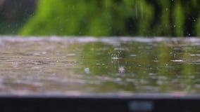 Raining on a park table stock footage