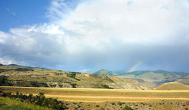 Raining Somewhere. Rainbow appears over distant mountains in Yellowstone National Park Royalty Free Stock Photo