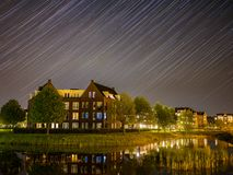 It is raining stars at Brandevoort. The reential area of Helmond called Brandevoort has some typical architectural buildings. At night the stars move across the stock images