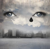 Raining tears. Surreal background representing two human eyes crying up from the clouds with a modern skyline city and water under Royalty Free Stock Photography