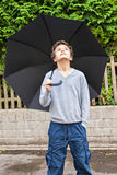 Is it raining?. A Teenage boy, outside, holding a black umbrelaa over him, he is looking up to see whether it is raining Royalty Free Stock Photography
