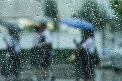 Raining and umbrella. Watching people gone by while is raning Royalty Free Stock Images