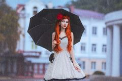 Raining weather. Autumn rain. Lonely unhappy girl in retro dress hold black umbrella. Raining in city. Wet umbrella against the ba royalty free stock images