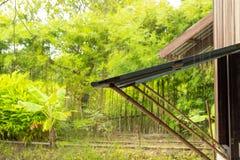 Raining window open, using bamboo poles to prop royalty free stock image