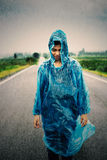 Raining with women on the road. Women wear rainwear standing in the middle on the road during the rain Stock Photography