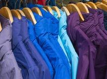 Rainproof jackets on a rack for sale. Rainproof jackets in bright colors on a rack for sale Royalty Free Stock Image
