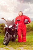Rainprotection for motorcyclist. Motorcycle rider puts on rain protection royalty free stock images