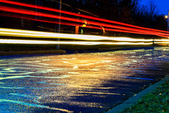 Rainstorm in the big city night, light from the shop windows reflected on the road  which cars travel. View  the level of asphalt. Rainstorm in the big city Royalty Free Stock Photo