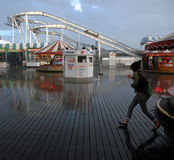 Rainstorm Brighton Pier uk. Rain Storms hit the UK over the Bank holiday weekend as people shelter and a girl runs for cover. Other usage is to highlight Stock Image