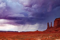 Rainstorm in the distance, behind Three Sisters rock formation in Monument Valley, Arizona. A dark, dramatic sky with distant rainfall is visible across an open royalty free stock photography