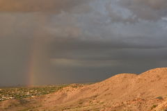 A rainstorm over the southern mountains of Phoenix, Arizona creates a rainbow. Stock Photo