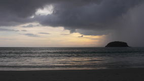 Tropical Island. In the distance, a rainstorm is moving in over a small tropical island right at sunset stock footage