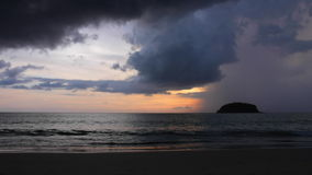 Rainstorm. A rainstorm is moving in over a small tropical island right at sunset stock video