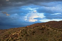 A rainstorm produces dark clouds over the southern mountains of Phoenix, Arizona . Royalty Free Stock Photo