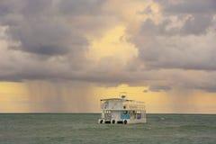 Rainstorm in a sea at sunrise Stock Photo