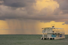 Rainstorm in a sea at sunrise Royalty Free Stock Image