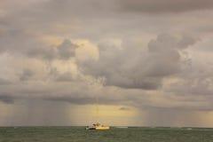 Rainstorm in a sea at sunrise Stock Photos