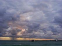 Rainstorm in a sea at sunrise Stock Image