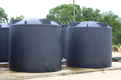 Rainwater Collection System. Water tanks holding rain water sit on a concrete slab Stock Photo