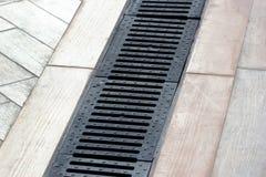 Rainwater drainage system on a sidewalk.  Stock Photos