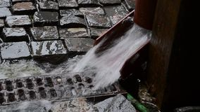 Rainwater Gutter. Lot of rainwater is flowing through the gutter to canalization. Sound included. A rain gutter is a narrow channel, or trough, forming the stock footage