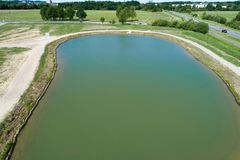 Rainwater retention basin with turquoise coloured water, taken diagonally from the air with a drone. Germany royalty free stock photo