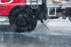 Rainwater spraying from motion truck wheels. city road during he Royalty Free Stock Photography