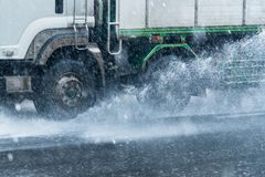 Rainwater spraying from motion truck wheels. city road during he Stock Photo