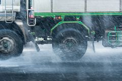 Rainwater spraying from motion truck wheels. city road during he Royalty Free Stock Image